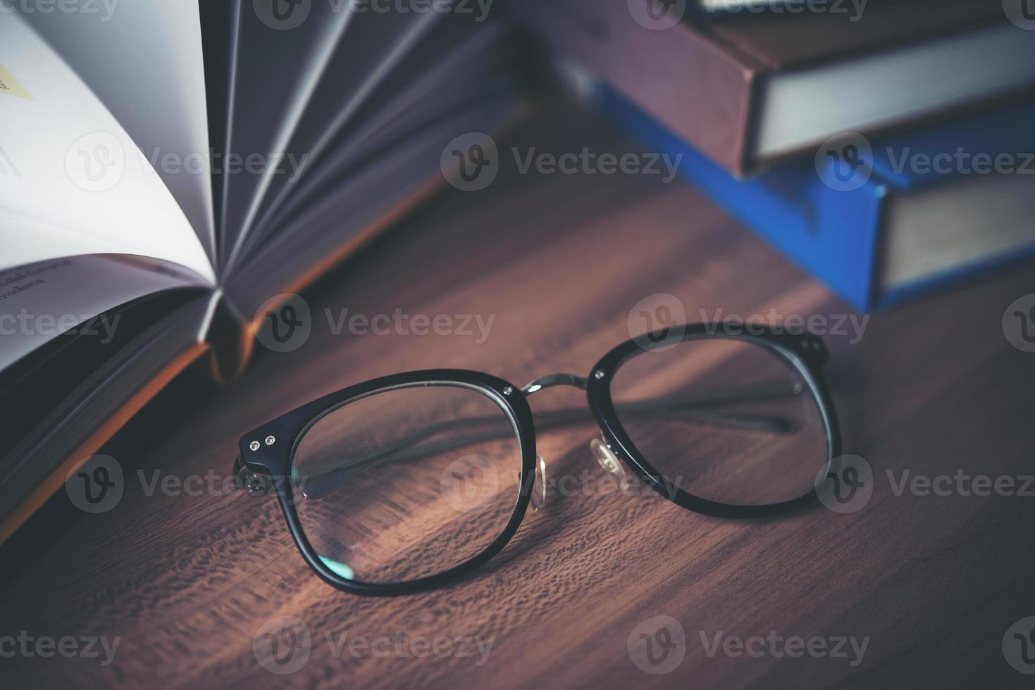 Glasses on wooden table with book photo