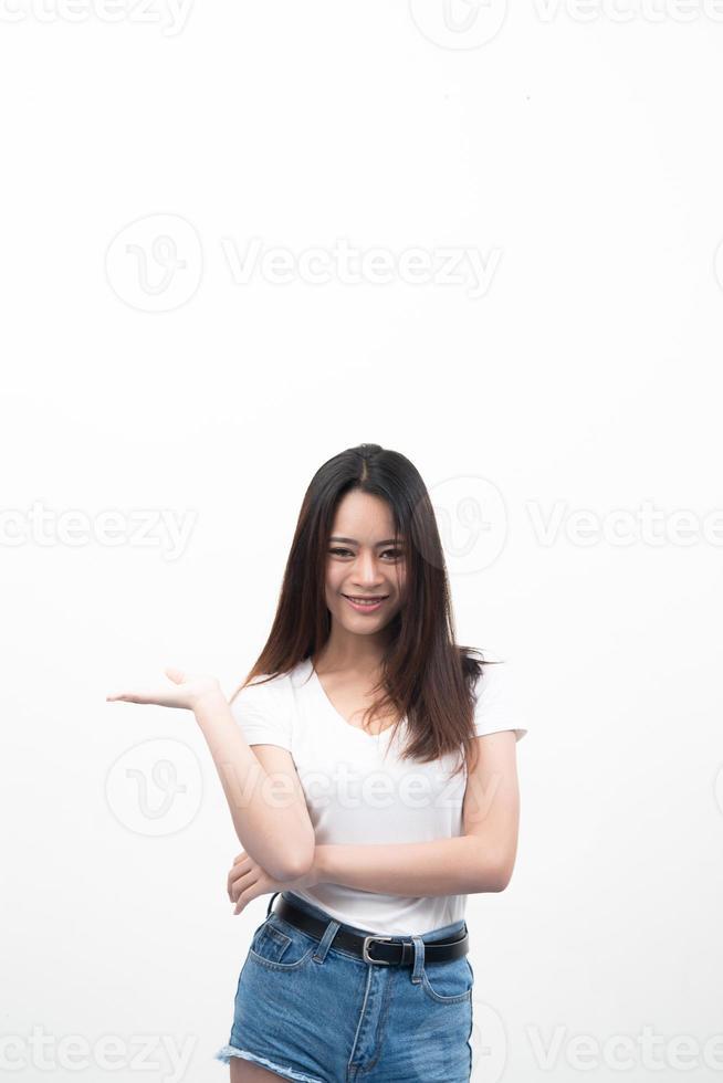 Hermosa joven asiática con la mano mostrando para publicidad aislado sobre fondo blanco. foto