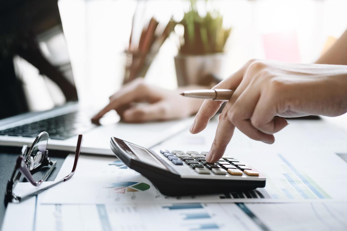 Business woman using calculator photo