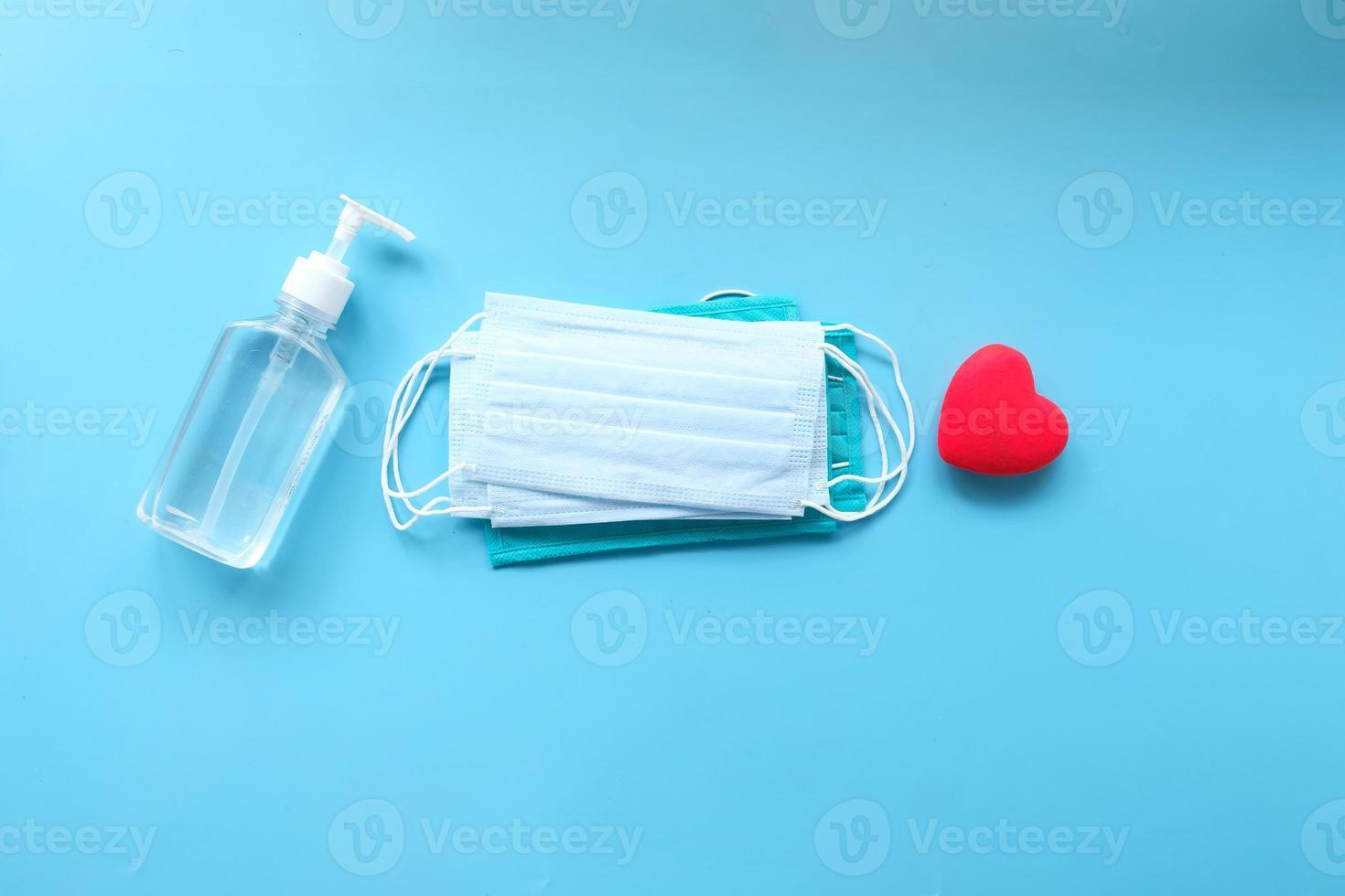 Mascarillas quirúrgicas con forma de corazón sobre un fondo azul. foto