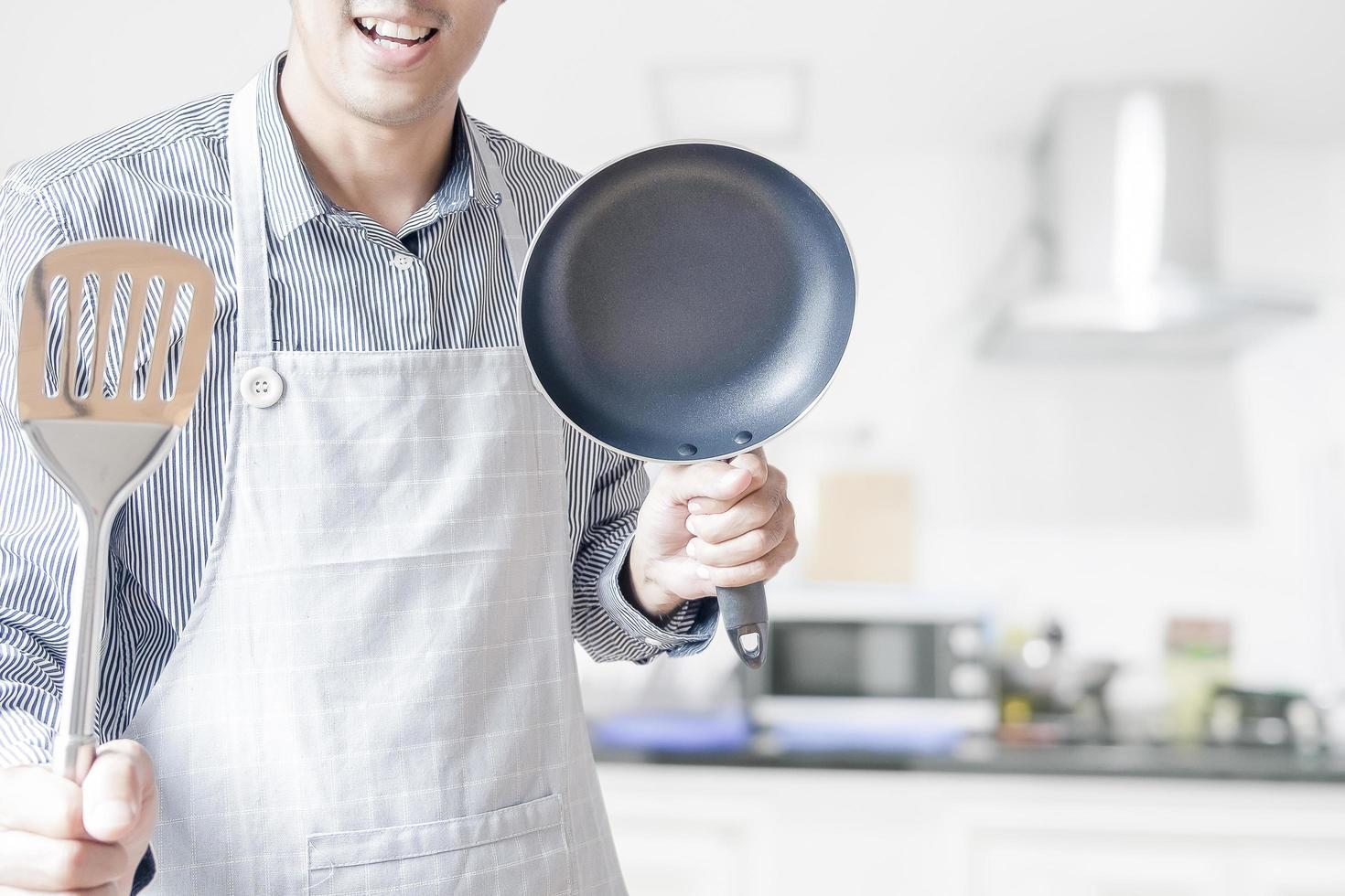 Man holding a pan and spatula photo