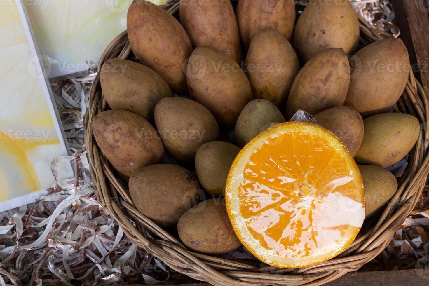 Sapodilla plums and orange in a basket photo