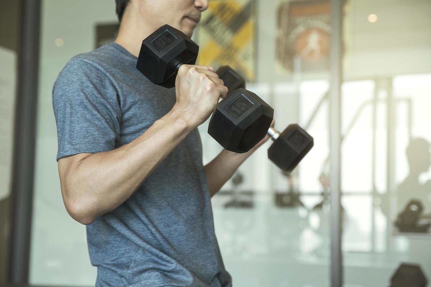 Man lifting dumb bells photo