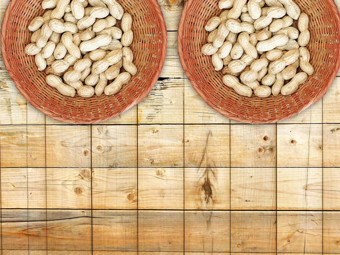 Peanuts in wicker baskets on wooden background photo