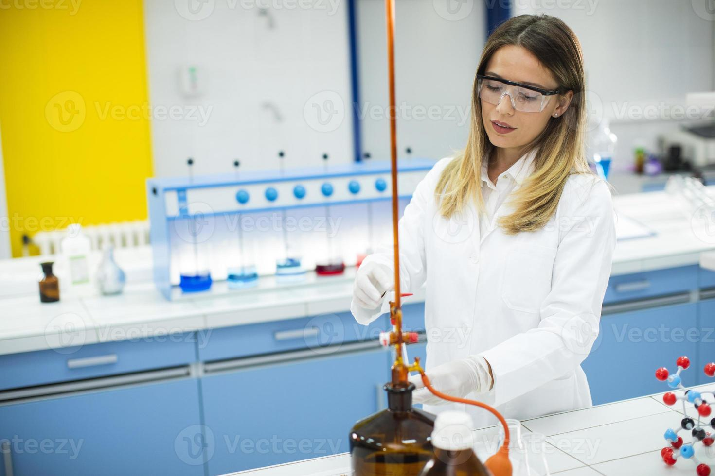 Female researcher in protective workwear standing in the laboratory and analyzing flask with liquid sample photo