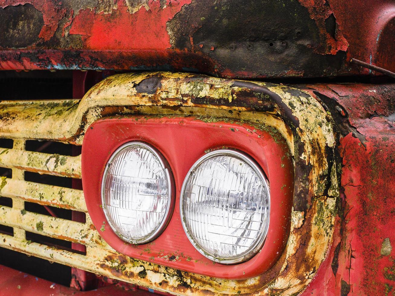 Detalle de los faros de un oxidado camión rojo y amarillo foto