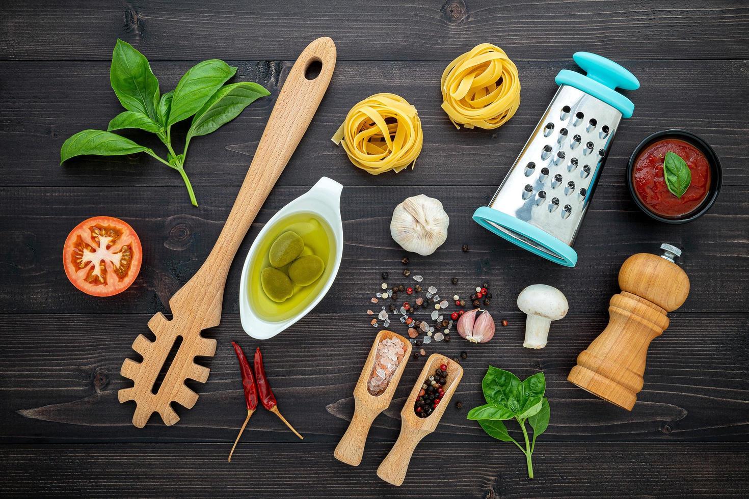 Flat lay of spaghetti ingredients on dark wood photo