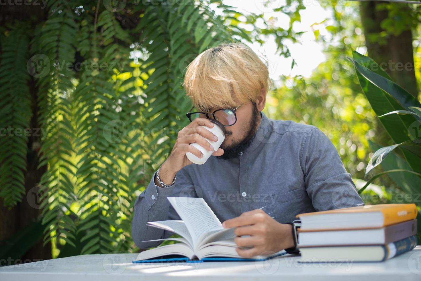 Hombre joven barba hipster tomando café mientras lee libros en el jardín de su casa con la naturaleza foto