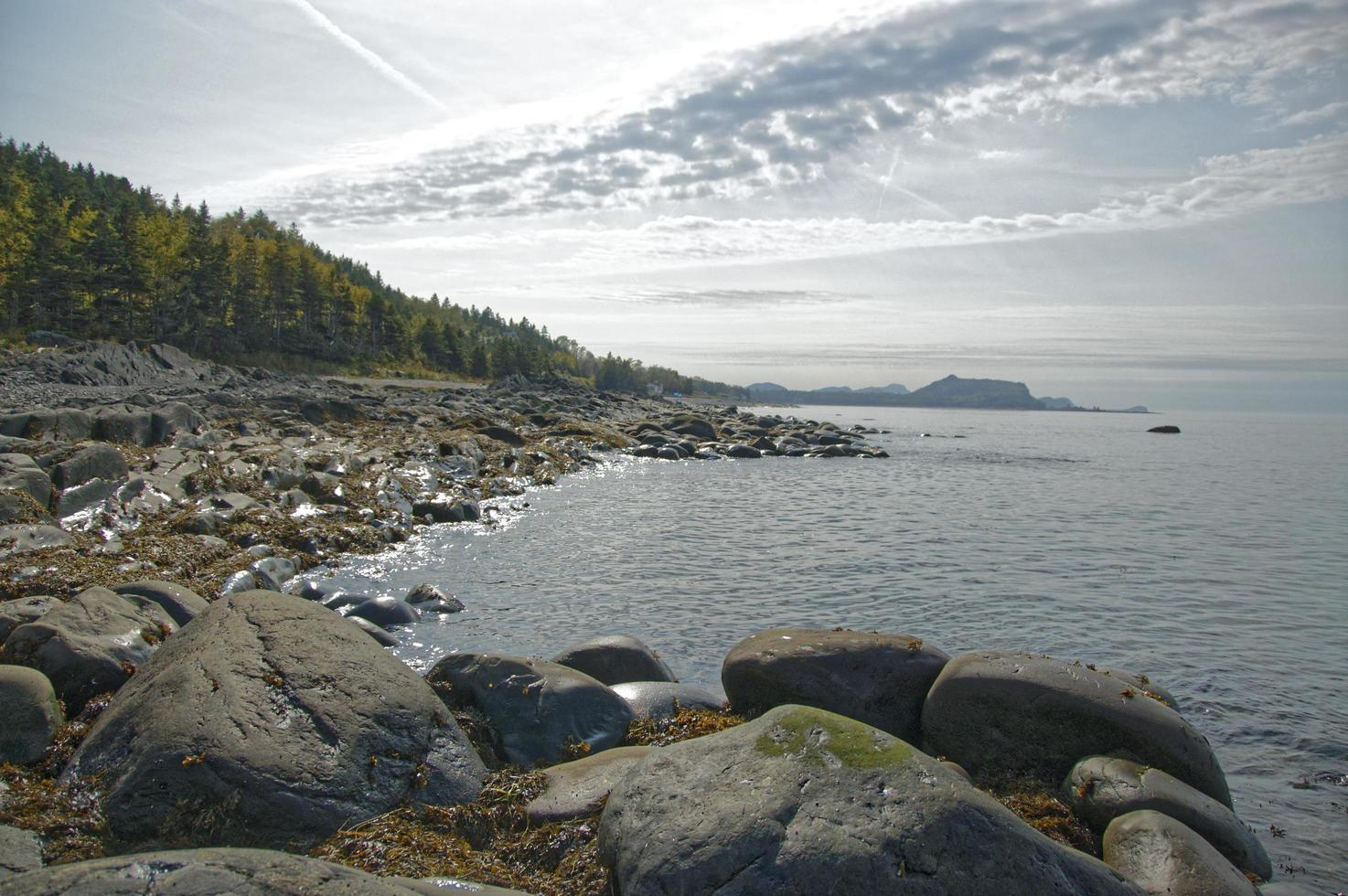 Rocks and shoreline next to body of water with cloudy blue sky in Quebec, Canada photo