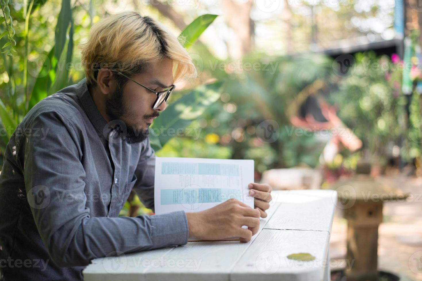 Joven hipster barbudo leyendo libros en el jardín de su casa con la naturaleza foto