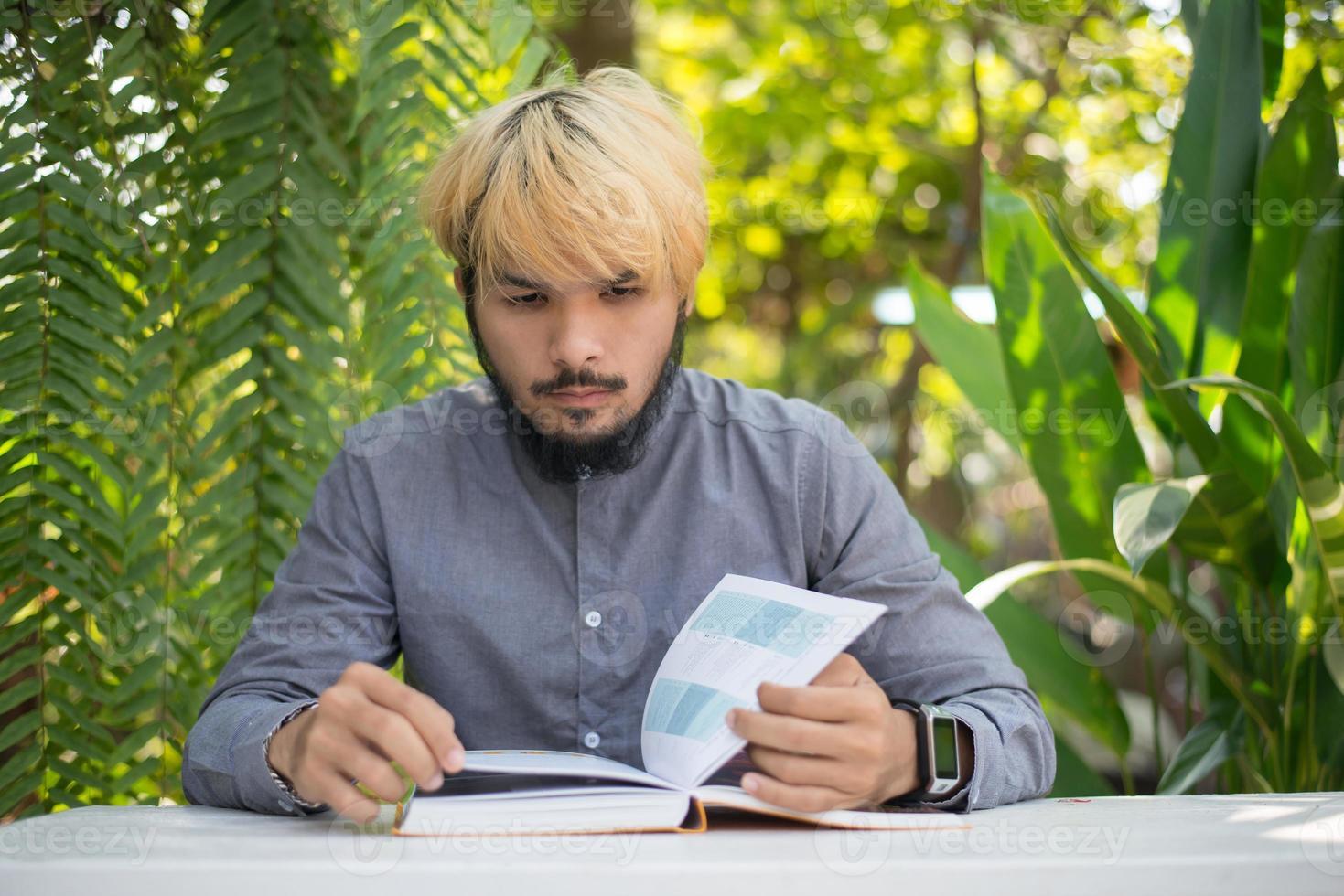 Joven hipster hombre barbudo leyendo libros en el jardín de su casa con la naturaleza foto