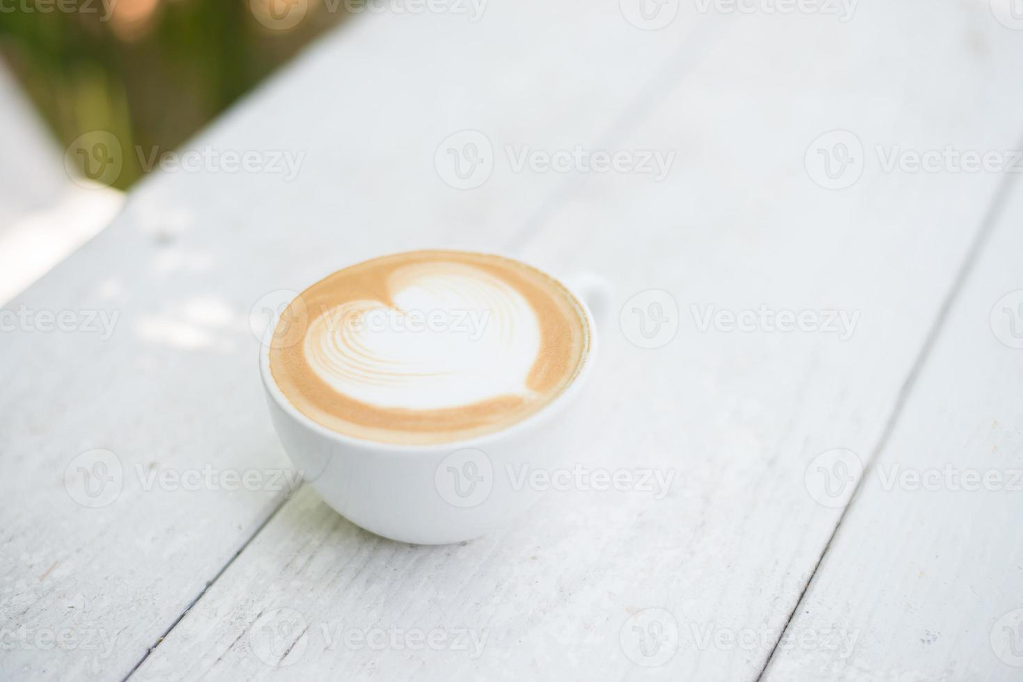 Cup of latte art heart shape coffee on white table photo