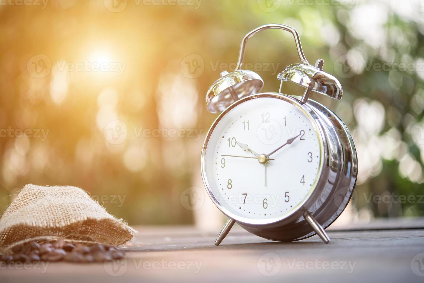 Retro alarm clock on wooden table photo