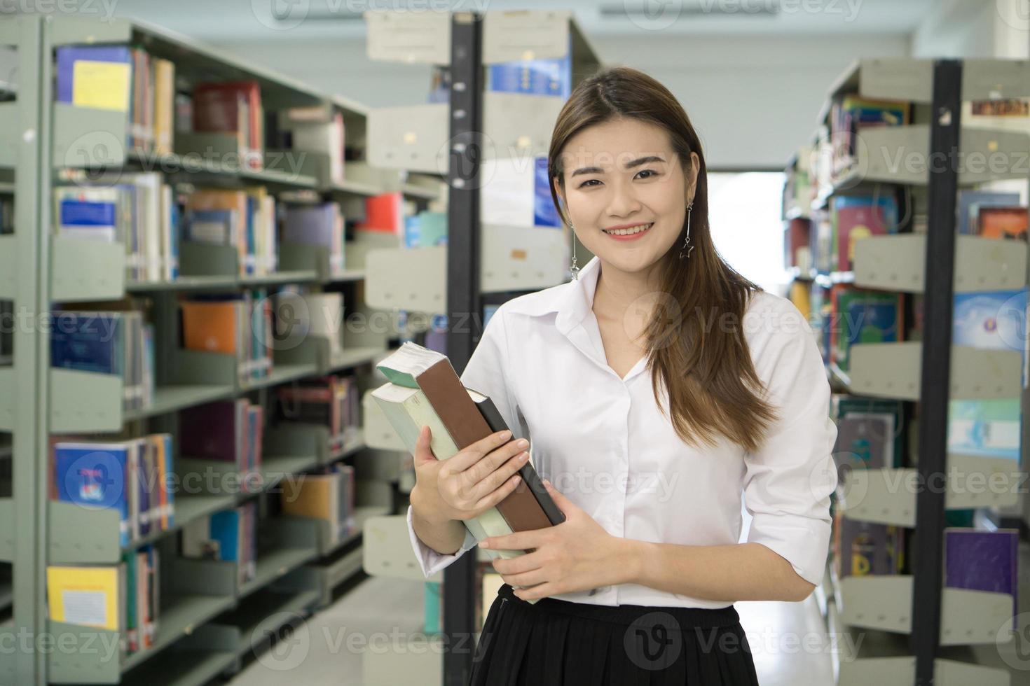 retrato, de, joven, estudiante, tenencia, libros, en, biblioteca foto