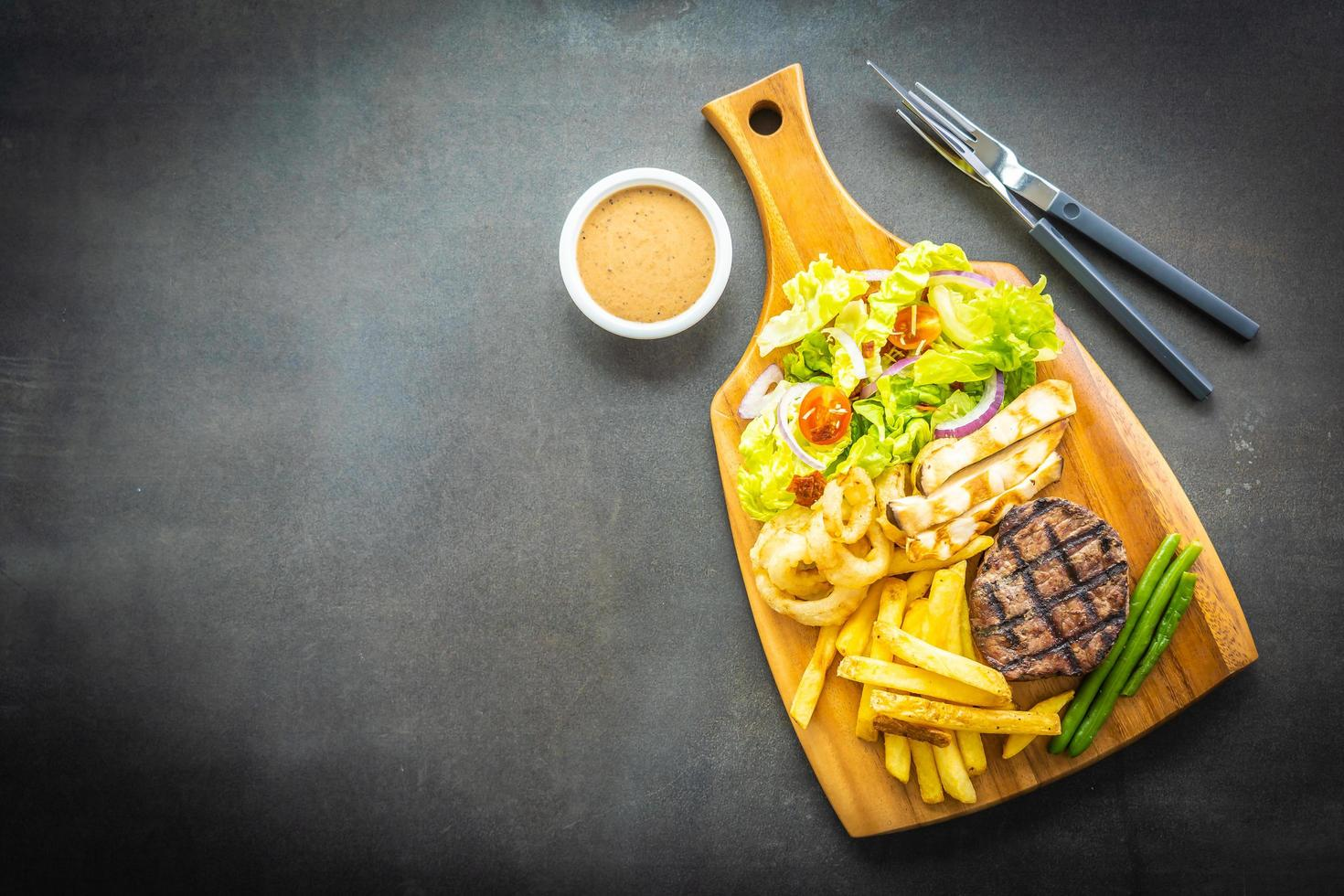Bistec de ternera a la plancha con patatas fritas, salsa y verduras frescas foto