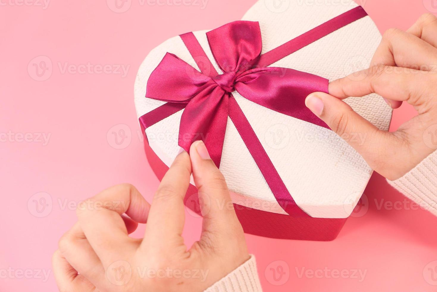 caja de regalo en forma de corazón sobre fondo rosa foto