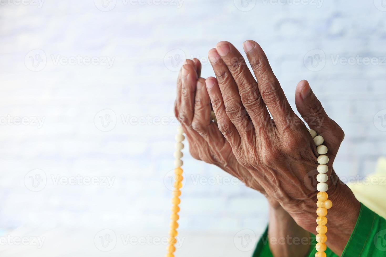 Close up of senior woman's hand praying at ramadan photo