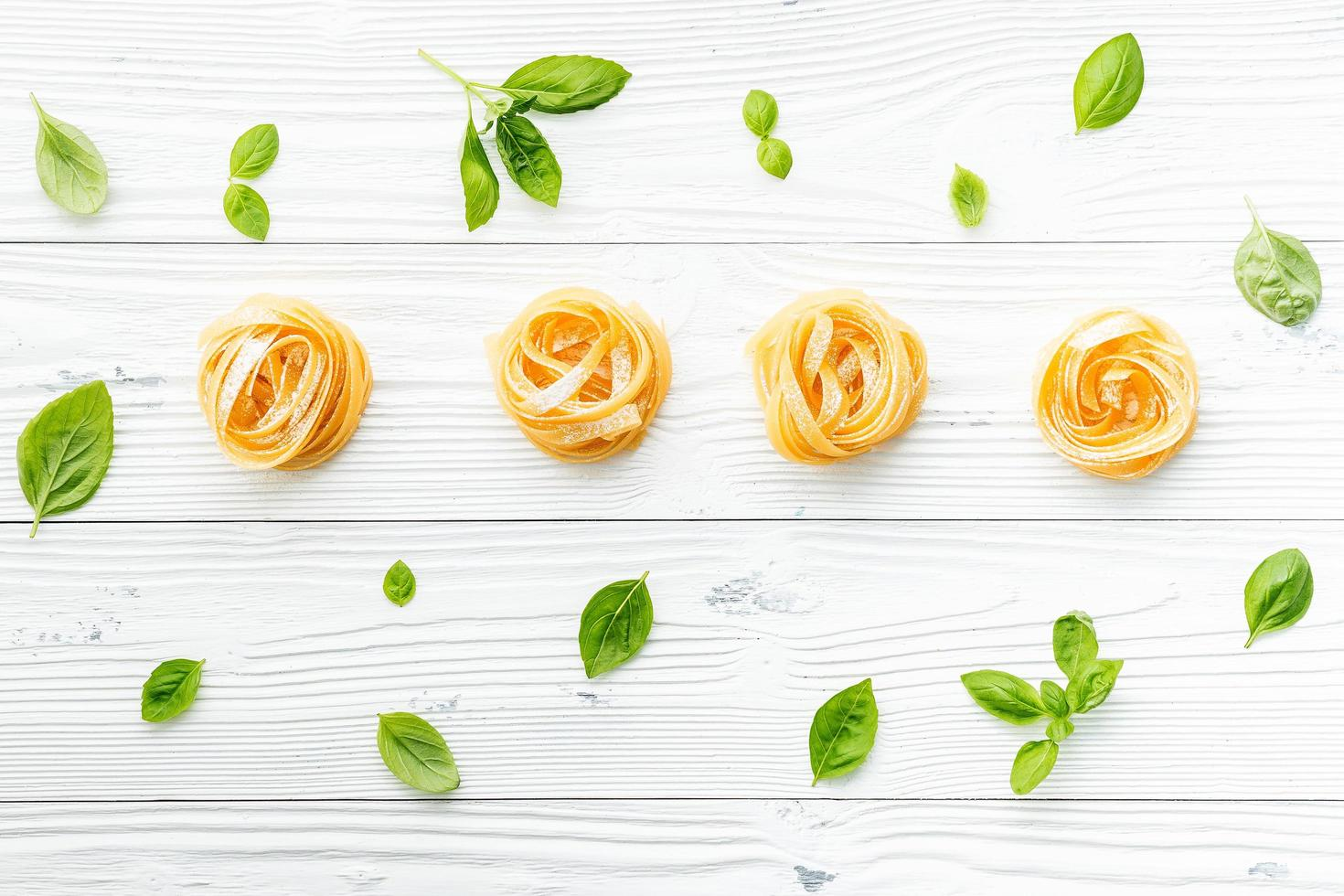 Fresh pasta and basil on a shabby white background photo