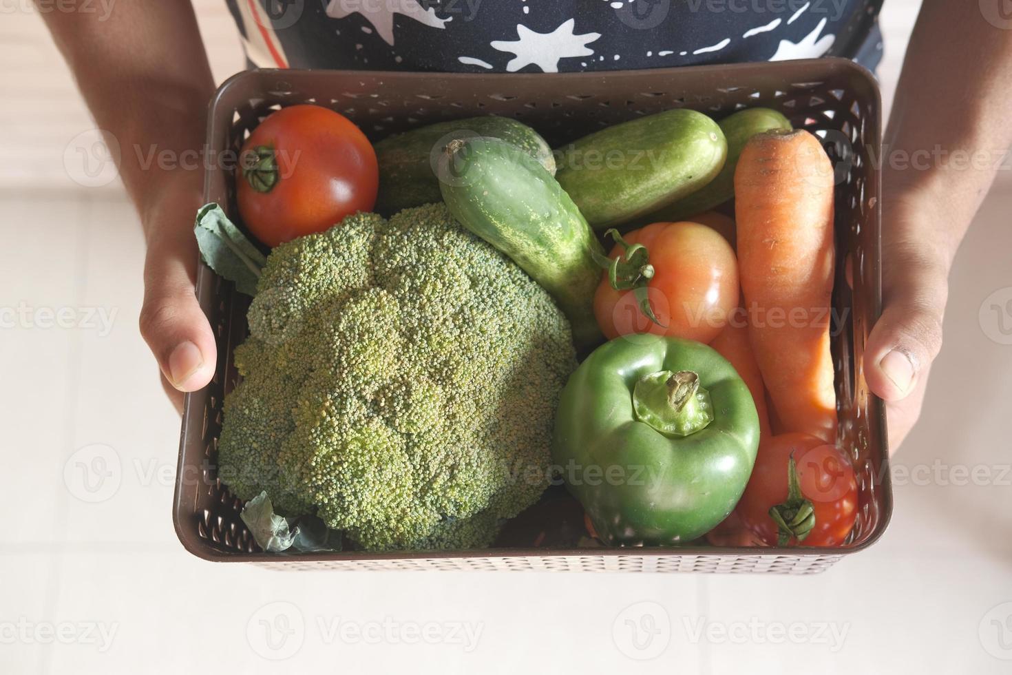 sosteniendo una canasta de verduras foto