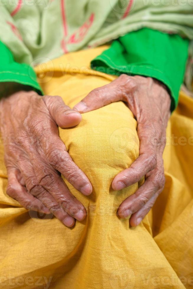 anciana sosteniendo la rodilla en el dolor foto