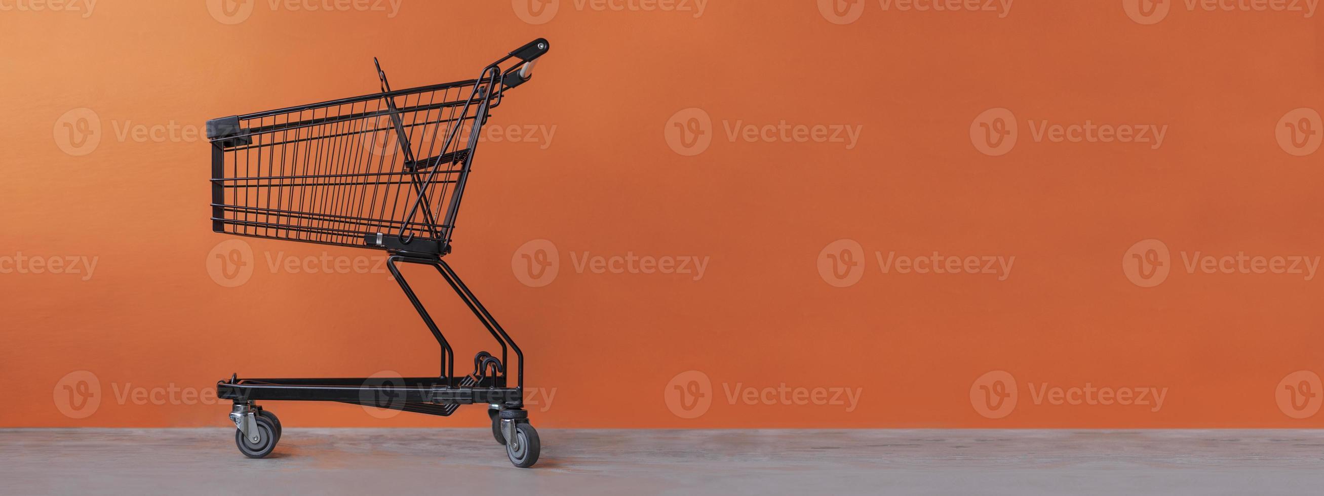 carrito de la compra sobre un fondo naranja foto