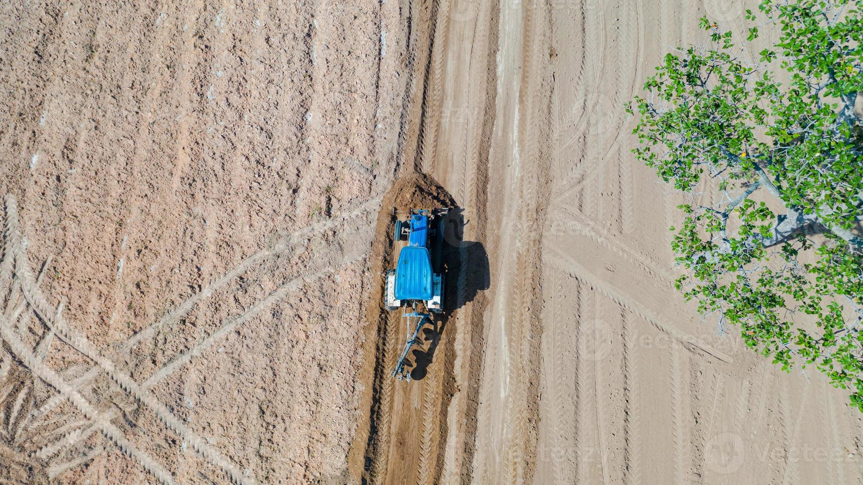 Top view of agricultural tractor vehicles working at field photo