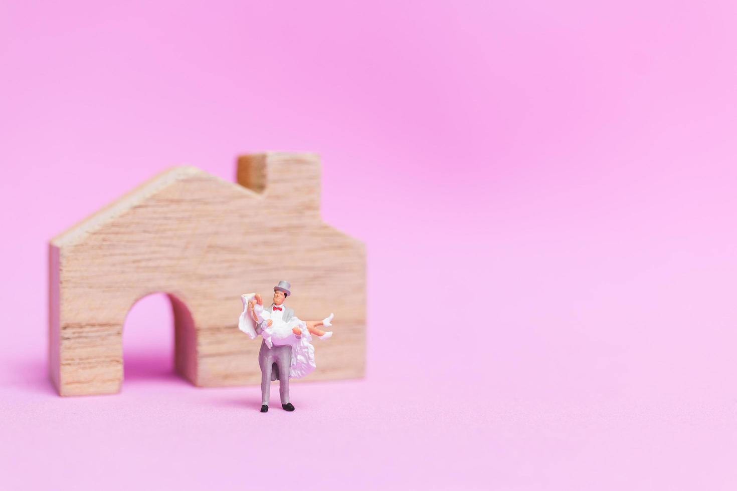Boda en miniatura de una pareja de novios sobre un fondo rosa, concepto de día de San Valentín foto