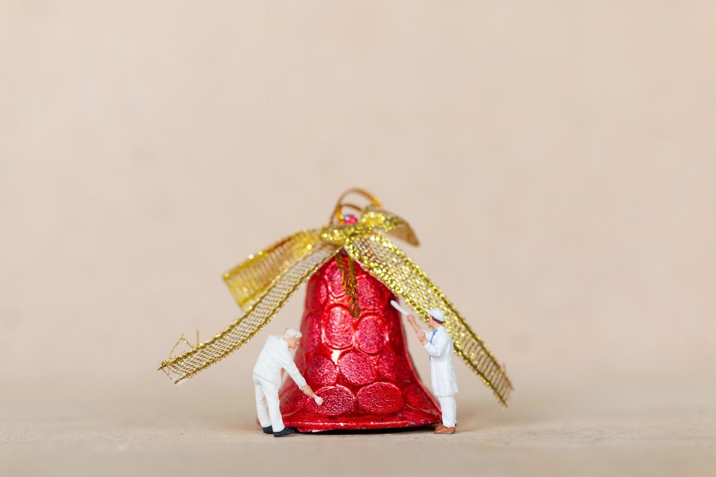 Trabajadores en miniatura pintando una decoración navideña, navidad y feliz año nuevo concepto foto