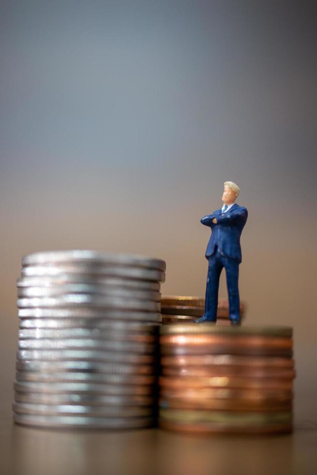 Pequeños empresarios en miniatura de pie con una pila de monedas, concepto de crecimiento empresarial foto