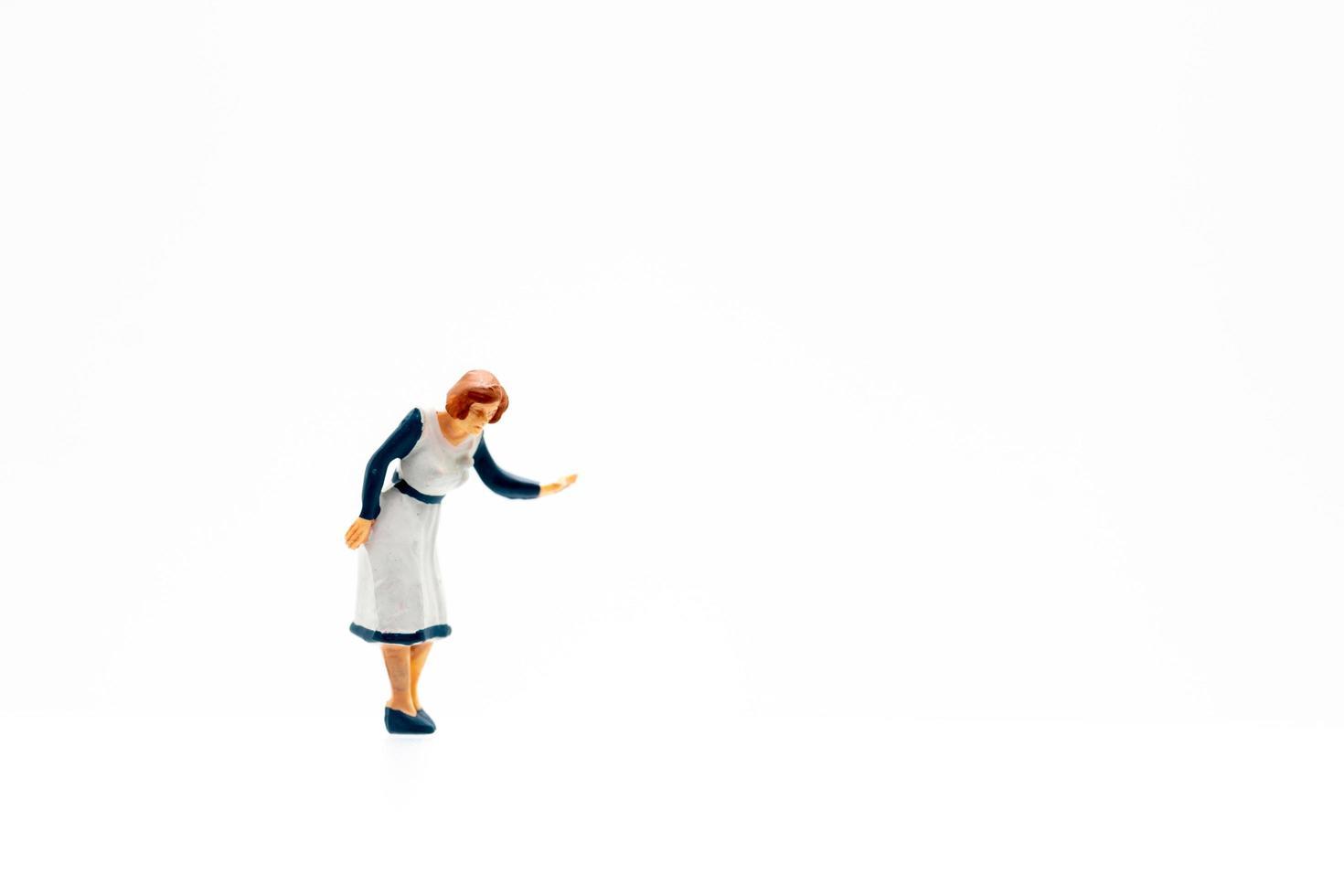 Una persona en miniatura de pie sobre un fondo blanco. foto