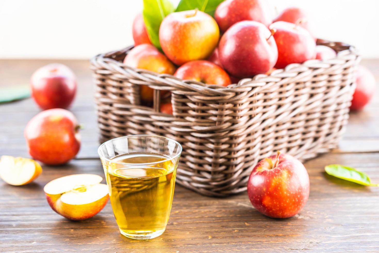 jugo de manzana en vaso y manzanas en la canasta foto