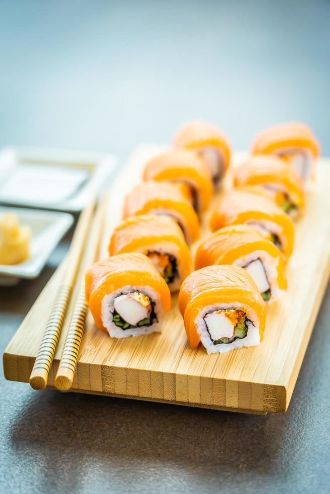Salmón pescado carne sushi roll maki en placa de madera foto