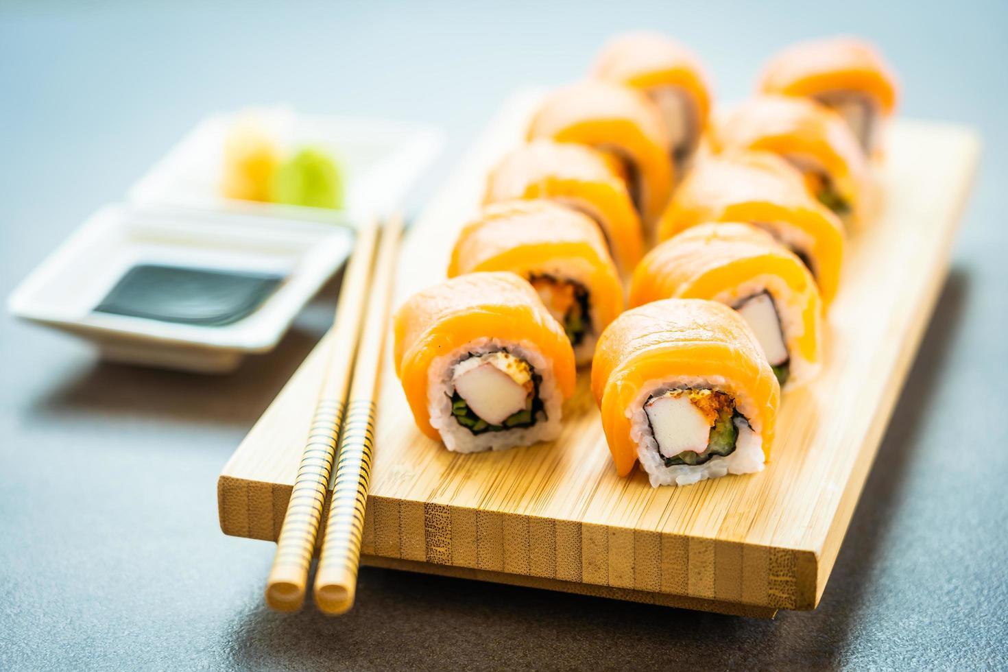 Rollos de sushi de salmón en placa de madera foto