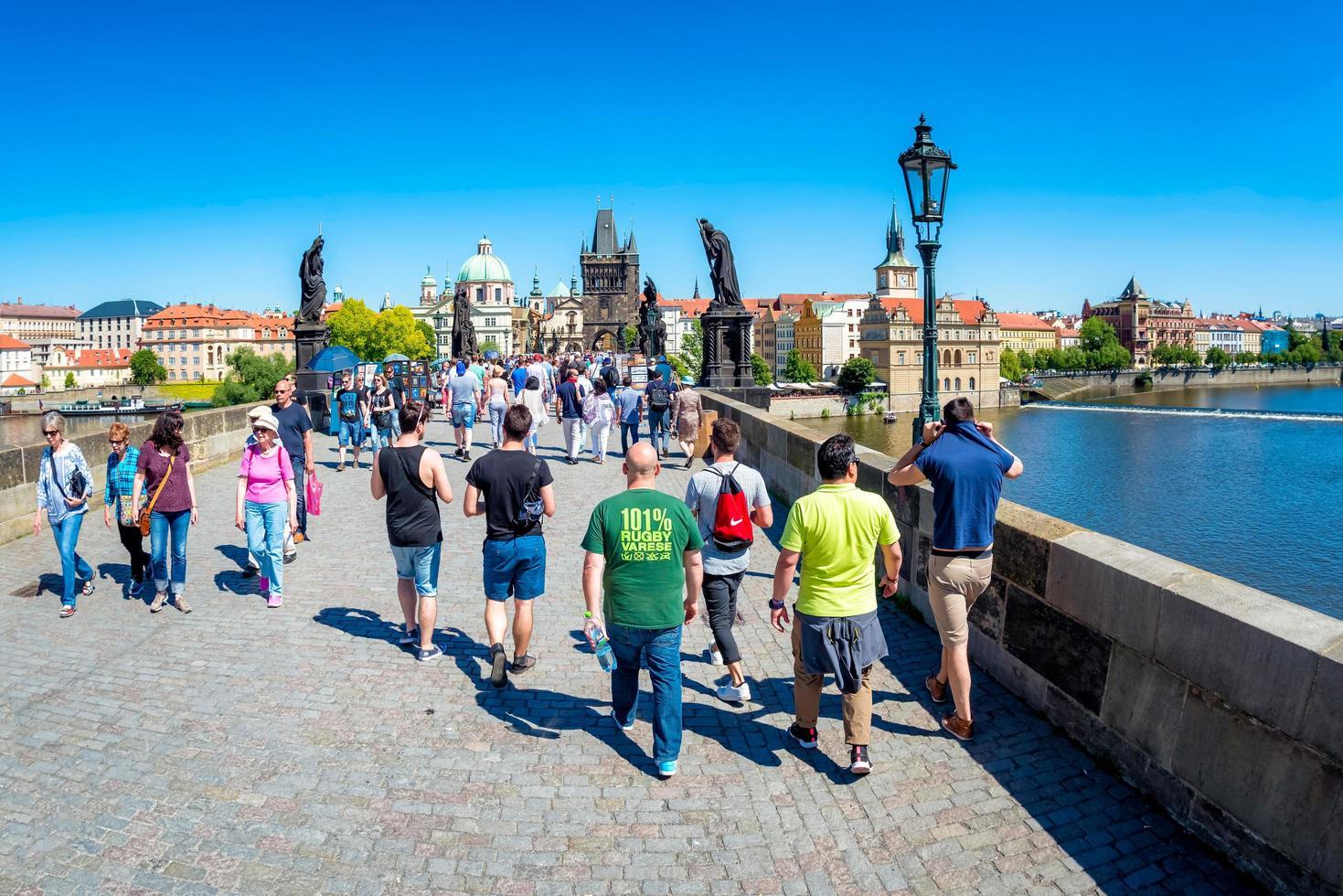 2017 praga, república checa - turistas que caminan por el puente de carlos mientras hacen turismo foto