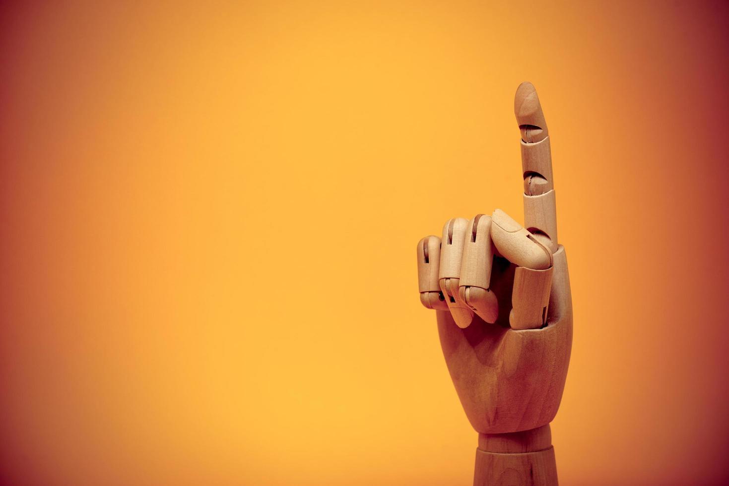 dedo de madera apuntando hacia arriba foto
