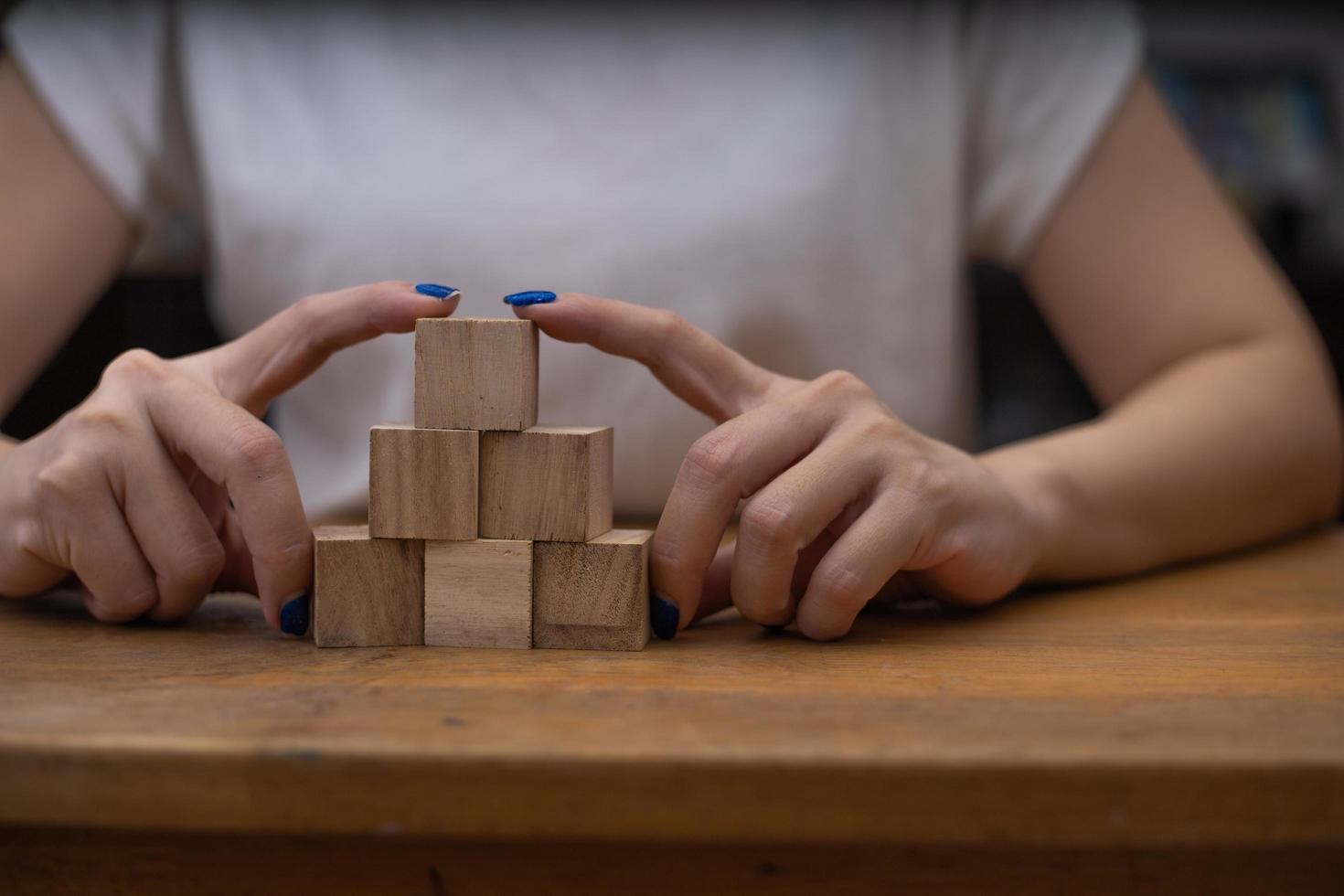 Woman stacking wooden blocks photo