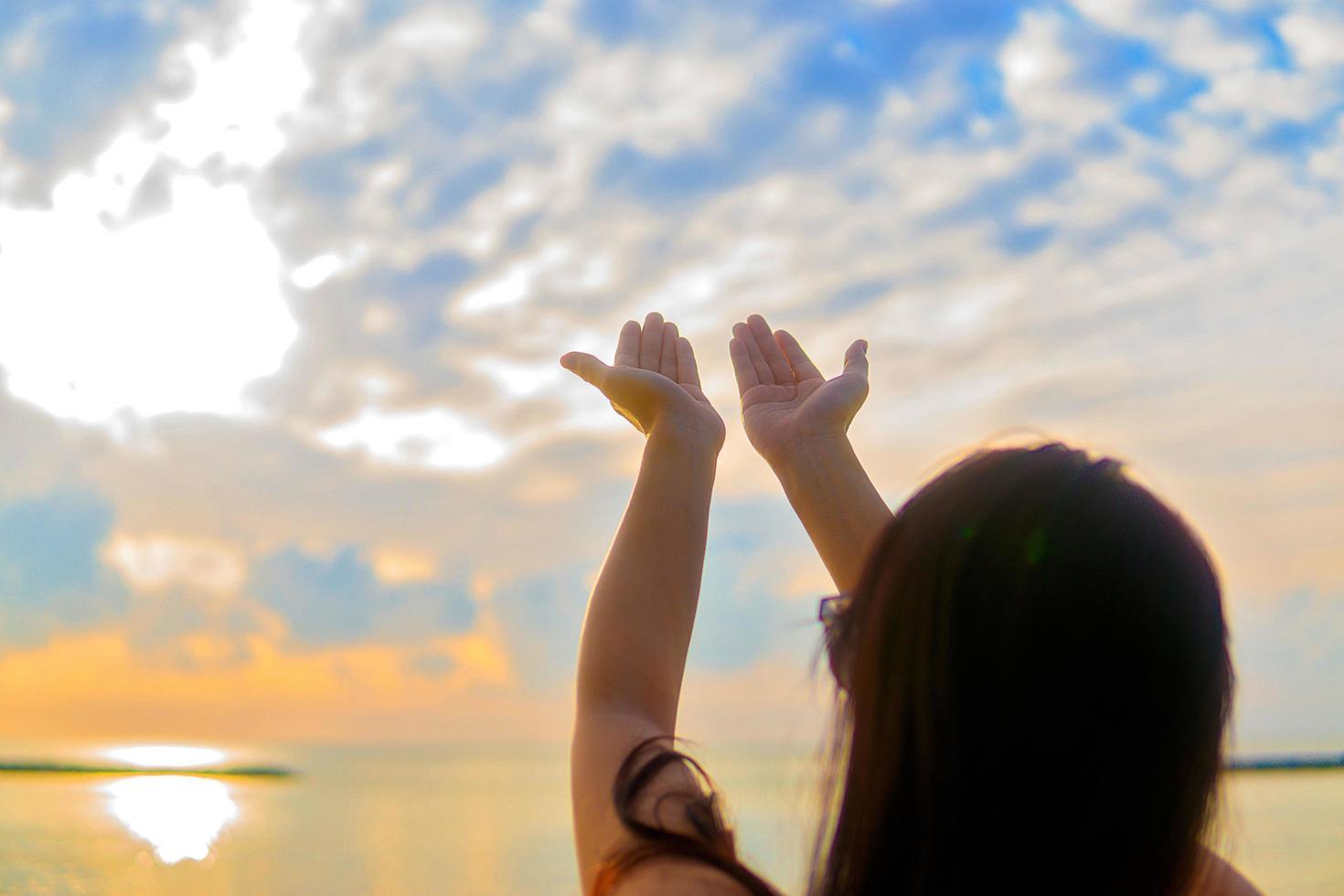 mujer rezando al atardecer foto