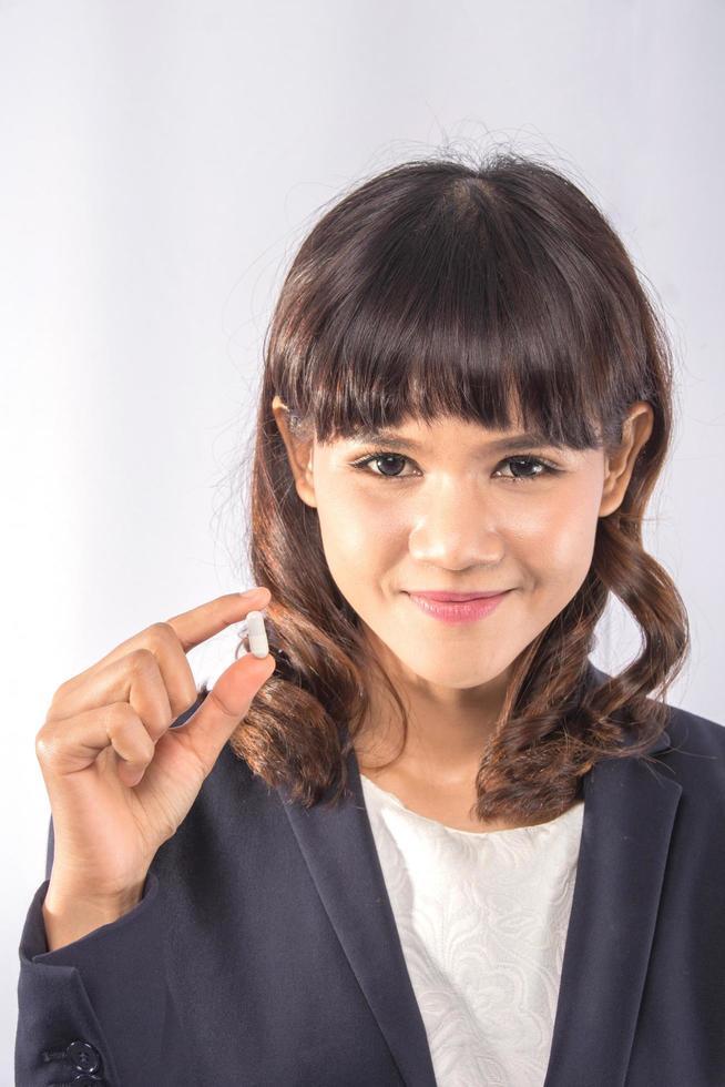 Woman holding a pill photo
