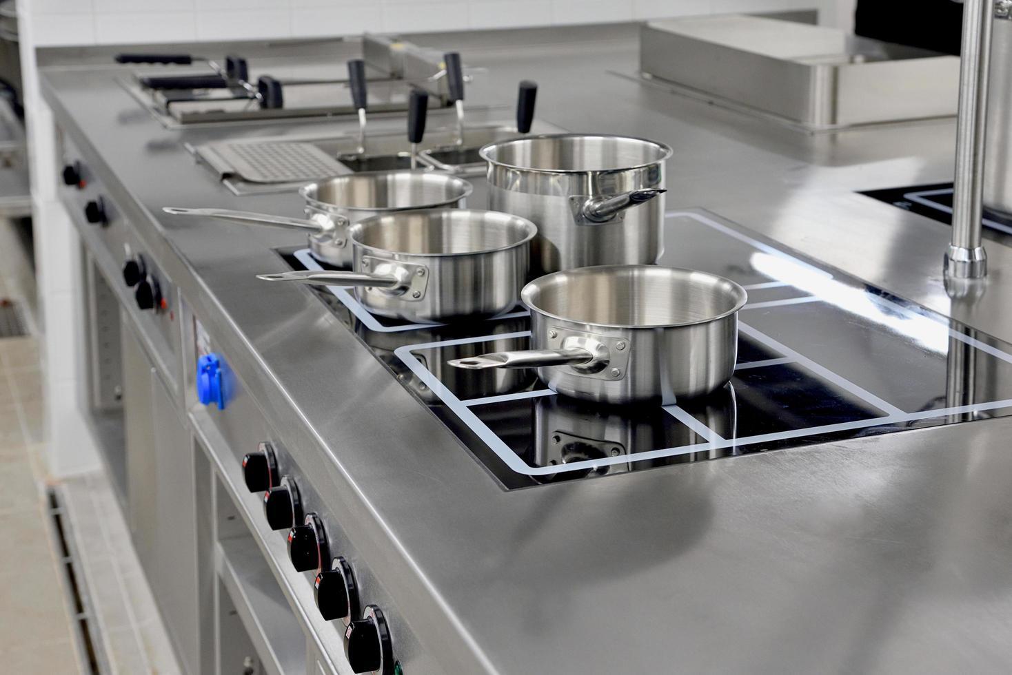 ollas de acero inoxidable construidas en la estufa en la cocina del restaurante foto