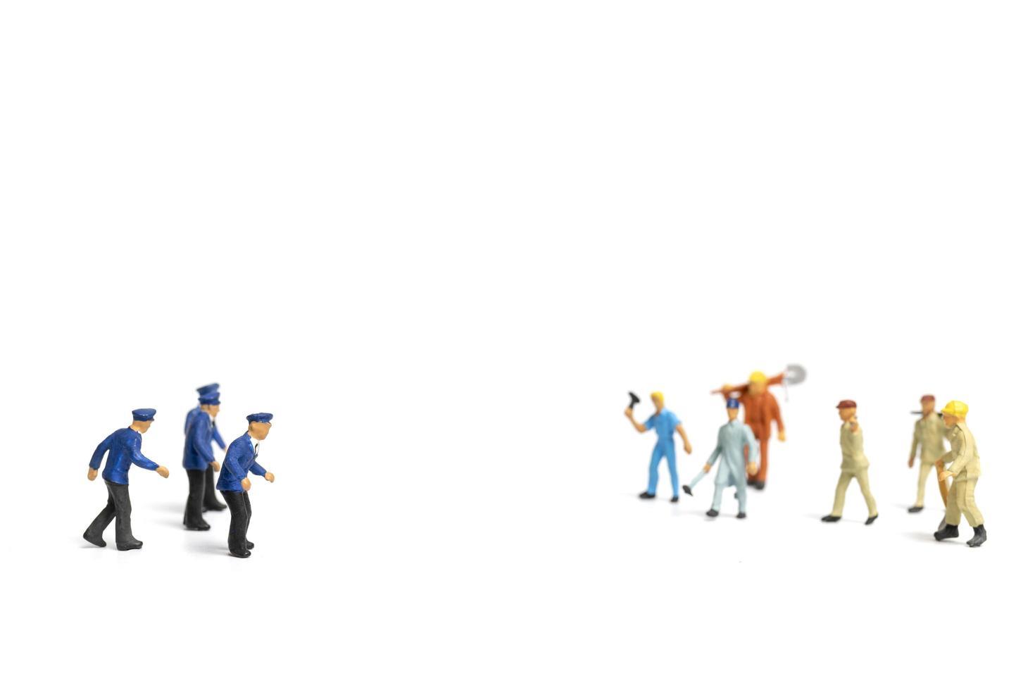 Policía en miniatura y una turba enojada sobre un fondo blanco. foto