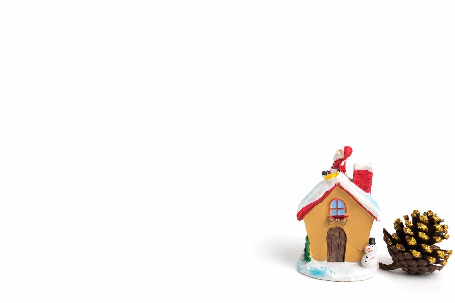 Escena navideña de estatuilla de Papá Noel sentado en un techo sobre un fondo blanco. foto