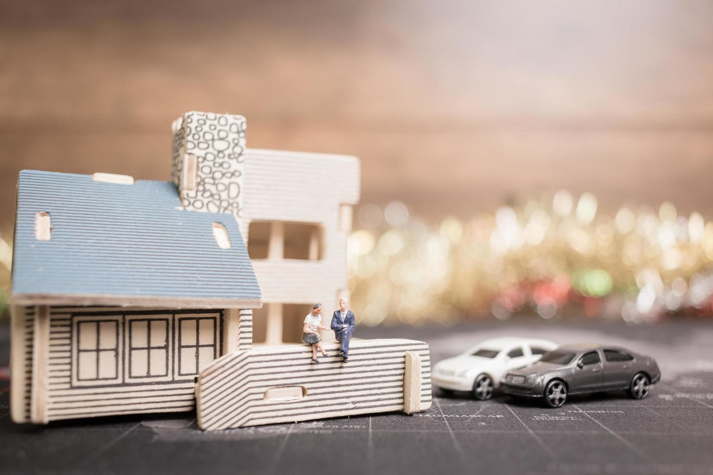 Gente en miniatura sentada en casa, inversión y crecimiento en concepto de negocio foto