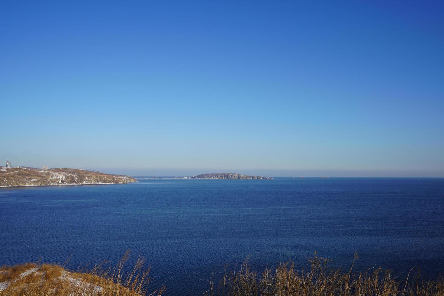 Paisaje marino de un cuerpo de agua y costa con un cielo azul claro en Vladivostok, Rusia foto