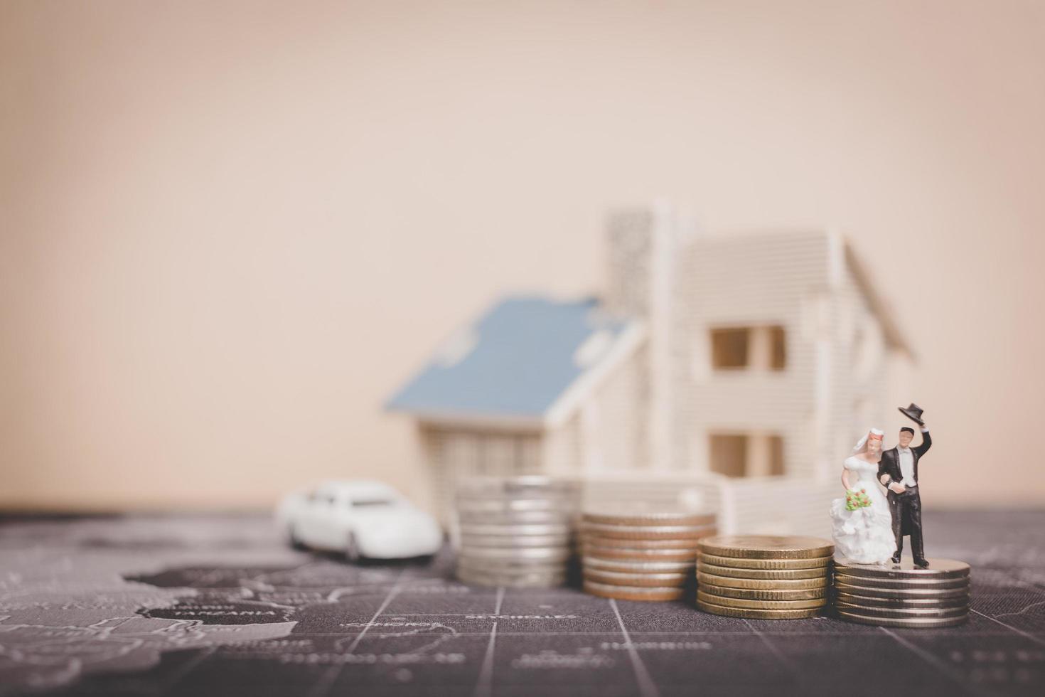 Novios en miniatura con monedas en frente de una casa, concepto de familia exitosa foto