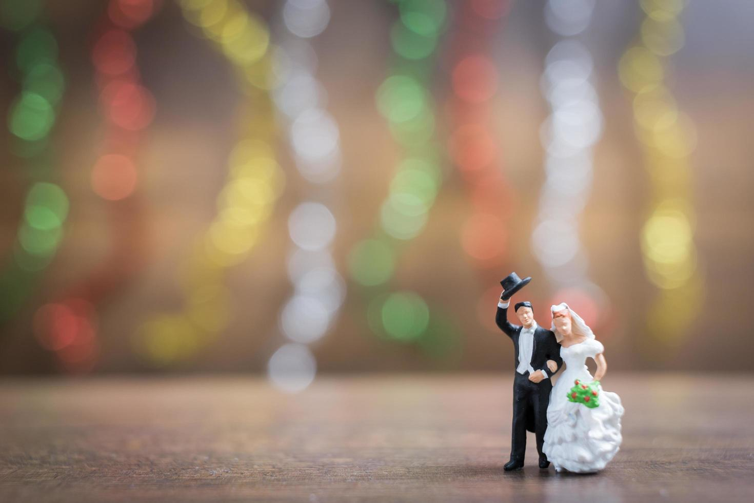 Miniature bride and groom on a wooden floor with colorful bokeh background, successful family concept photo