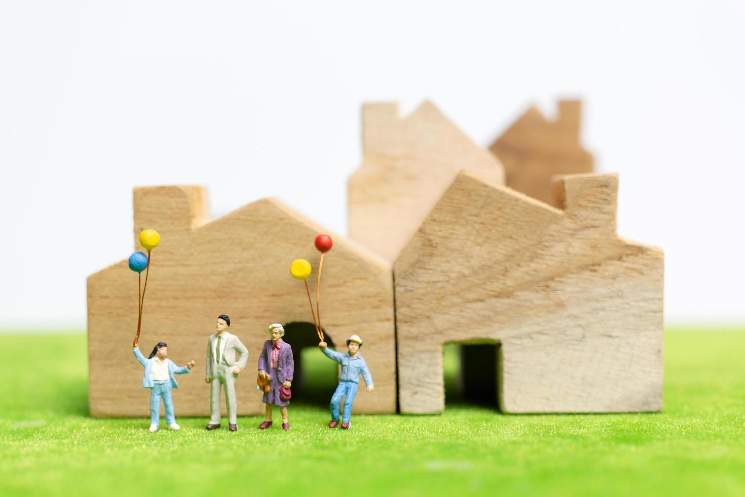 Miniature family walking in a field with balloons, happy family time concept photo