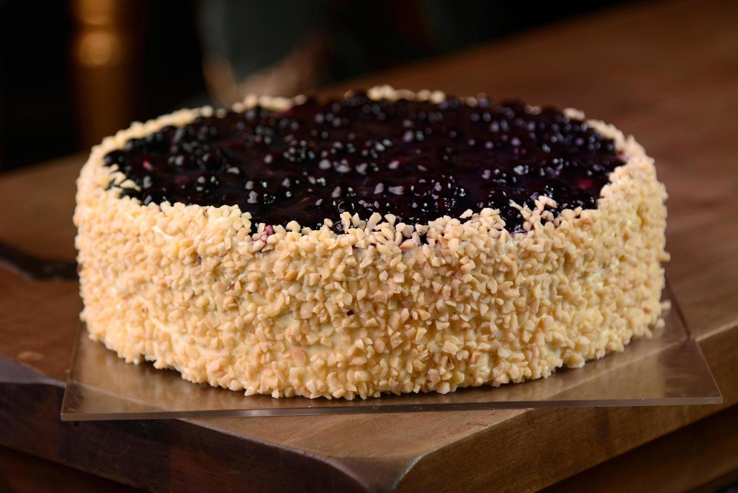 Close up of blueberry pie with almonds on wooden table photo