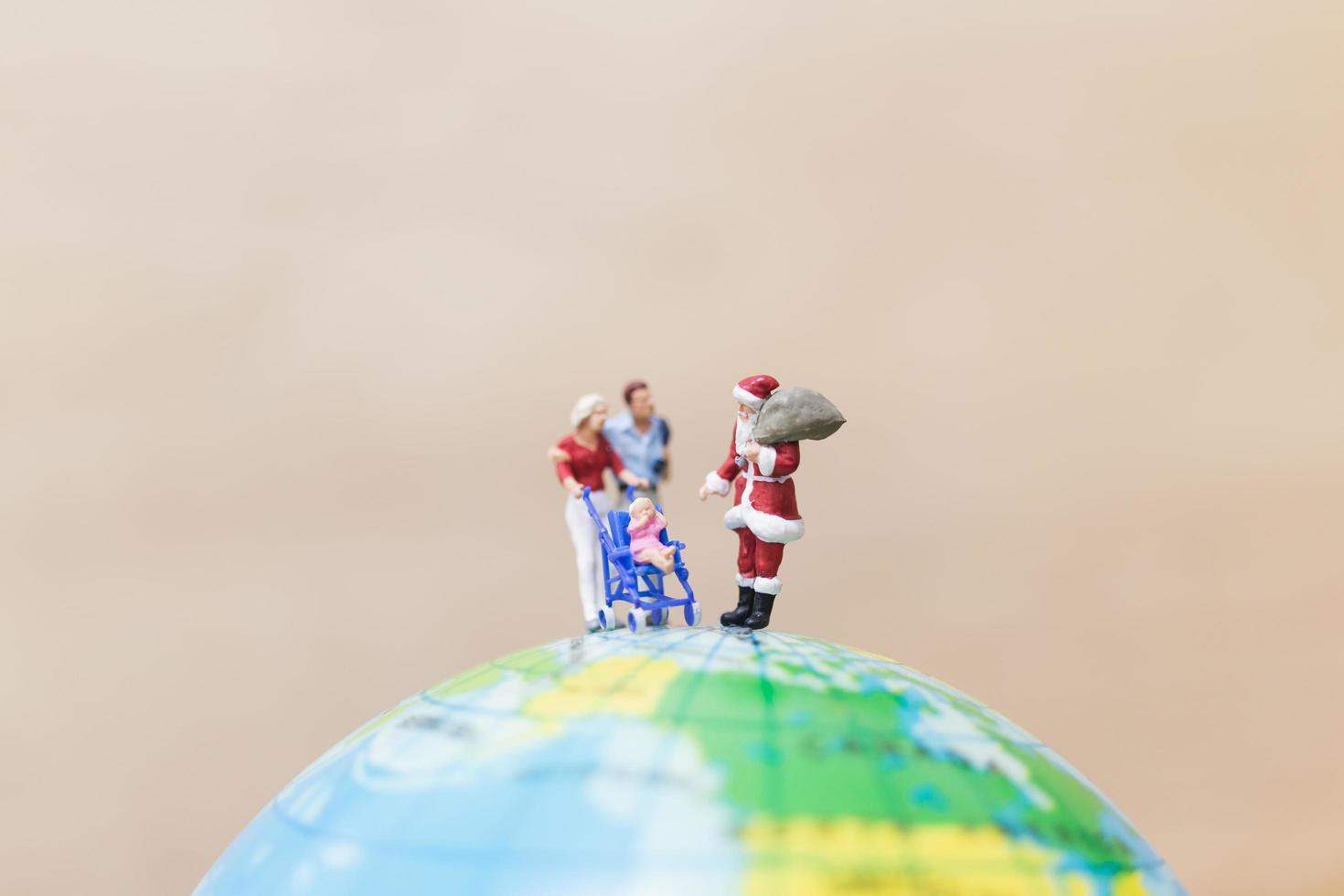 Miniature Santa Claus holding gifts for kids on a globe, Merry Christmas concept photo