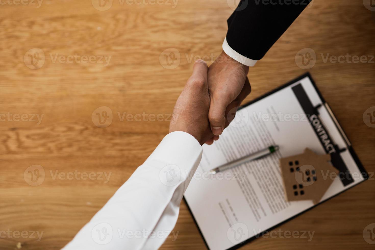 dos hombres de negocios dándose la mano sobre el contrato foto