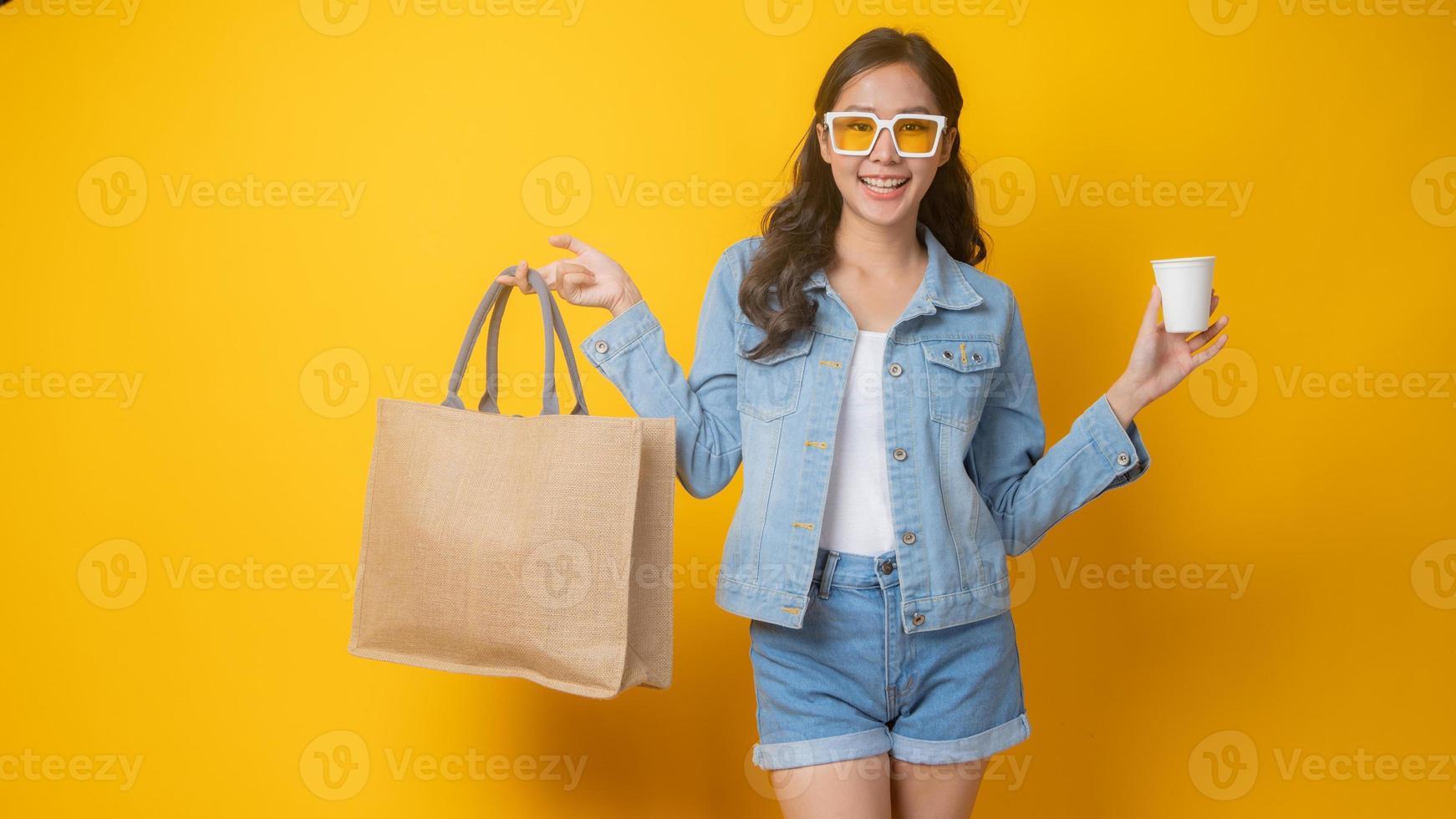 Mujer asiática sosteniendo una bolsa de papel y un vaso de papel blanco sobre fondo amarillo foto
